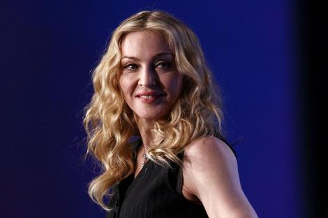 Madonna, zâmbitoare, cu părul desprins și ondulat, îmbrăcată în negru