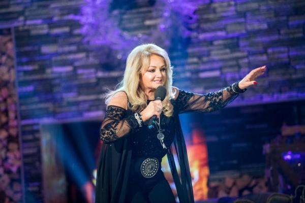 Bonnie Tyler, într-un concert, îmbrăcată în rochie neagră