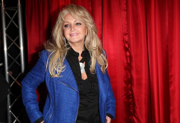 Bonnie Tyler, îmbrăcată într-un sacou albastru și bluză neagră, are părul blond, desprins