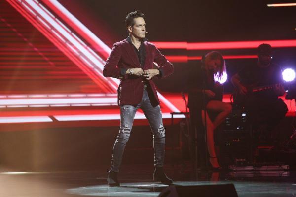 Ștefan Bănică, pe scena X Factor, purtând o cămașă vișinie