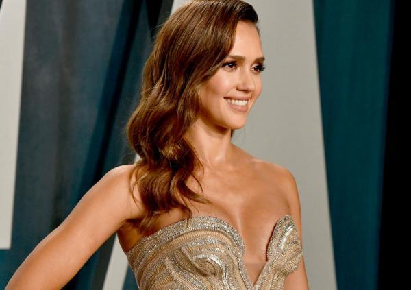 Jessica Alba, îmbrăcată într-o rochie cu decolteu, are părul desprins și zâmbește