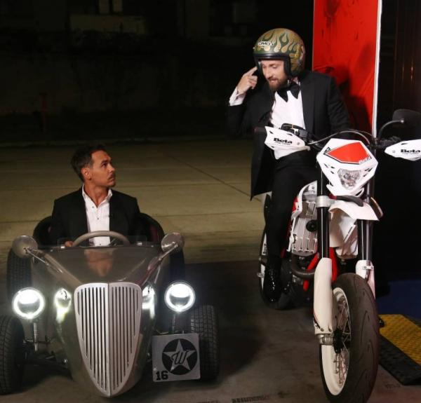 Dani Oțil pe motocicletă, uitându-se de sus la colegul său Răzvan