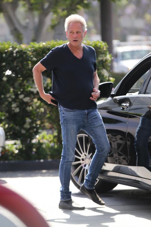 Lindsey Buckingham fotografiat pe stradă, îmbrăcat în blugi și tricou