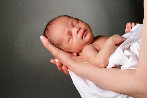 Bebeluș ținut în mâini, are ochii închiși, doarme