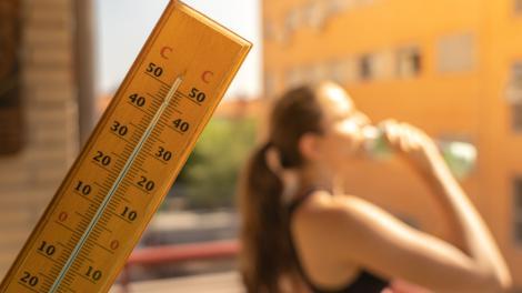 Un termometru și o fată care bea apă din sticlă
