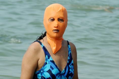"""Femeie purtând """"Facekini"""", în apă"""