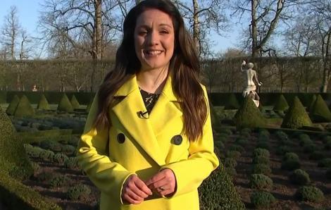 laura tobin in palton galben, prezentand rubrica meteo intr-un parc