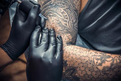 imagine cu bratul tatuat al unui barbat