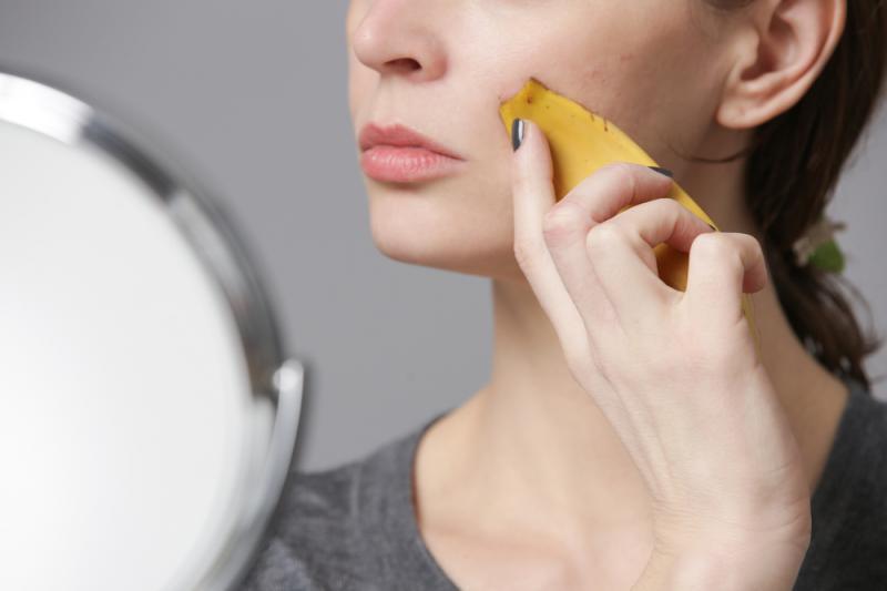 o femeie foloseste cojile de banane pentru ten