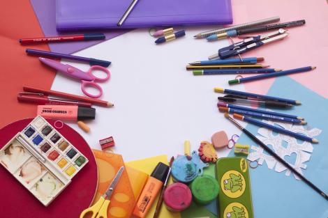 acuarele, creioane si pensule puse pe o plansă colorata