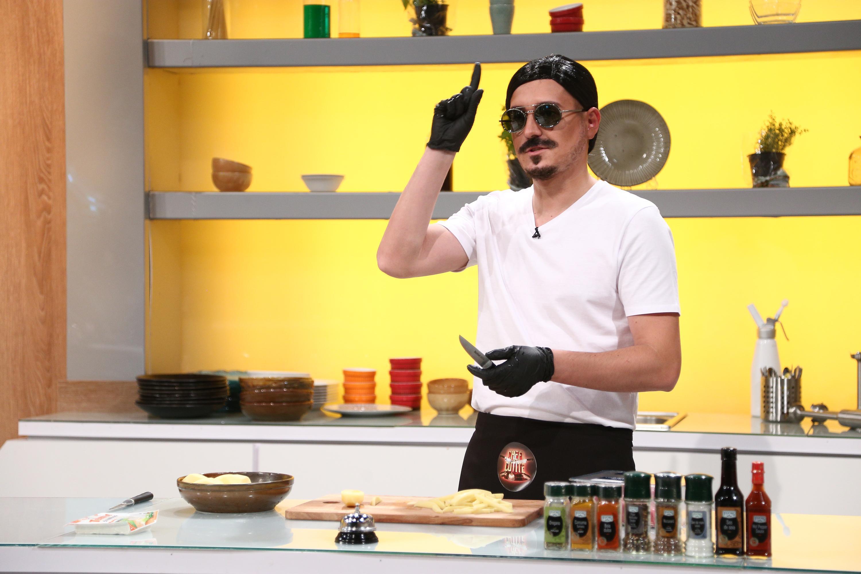 George Tănase într-un tricou alb și ochelari de soare, prepara mancare în bucătăria chefi la cuțite