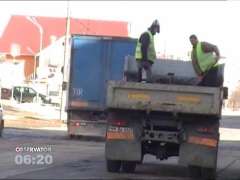 Metoda inedita de asfaltare: Doi muncitori arunca bitum peste gropi, direct din bena unui camion
