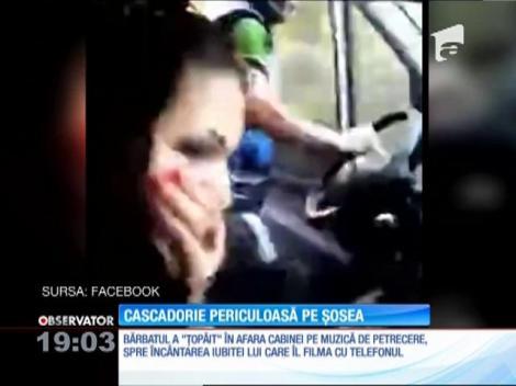 Cascadorie periculoasă. Dansează cu o mână pe volan, în afara camionului care rulează cu viteză pe şosea!