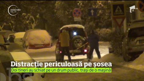Doi tineri din Baia Mare au ales să practice schiatul pe şosea, traşi de un autoturism