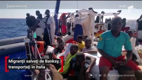 Migranții salvați de artistul stradal Banksy, transportați în Italia